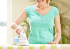 Close up of happy woman with iron ironing at home Royalty Free Stock Images