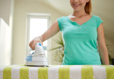 Close up of happy woman with iron ironing at home Royalty Free Stock Photos