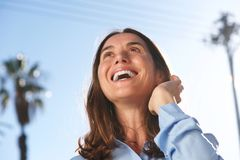 Close up happy  woman laughing Wirth hand in hair outside. Close up portrait of happy  woman laughing Wirth hand in hair oute Royalty Free Stock Photos