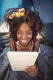 Close up of happy woman using digital tablet while lying down in tent. At camp Royalty Free Stock Photo