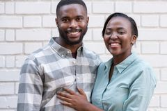 Smiling African couple standing together in the city. Close up of happy young African couple hugging while standing together in front of a brick wall in the city stock photos