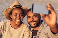 Content young African couple taking selfies together at the beach. Close up of happy young African couple sitting together on a sandy beach enjoying a glass of royalty free stock images