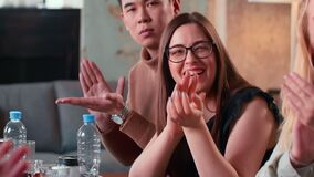 Close-up happy young Asian man and Caucasian woman applause and smile sitting at modern office business meeting table.
