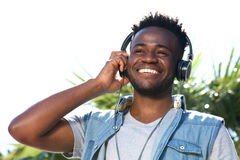 Close up happy young black man listening to music with headphones Royalty Free Stock Image