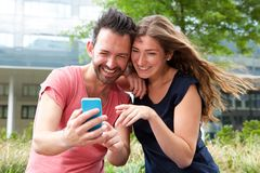 Close up happy young couple sitting together with mobile phone Royalty Free Stock Images