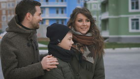 Close up of happy young family in warm clothing standing together on the street smiling. Father and mother are laughing stock footage