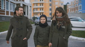 Close up of happy young family in warm clothing are walking together on the street laughing and talking. Father and stock video