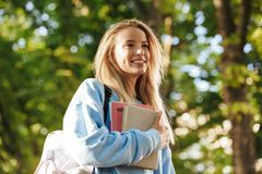 Close up of happy young girl student with backpack. Carrying books, walking at the park Stock Photo