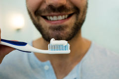 Close-up of happy young man holding toothbrush with toothpaste. At home Royalty Free Stock Photography