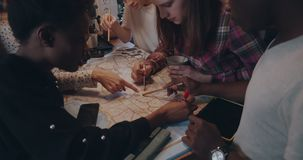 Close-up happy young multiethnic friends sit together looking at big map with pencils on kitchen table slow motion. stock video