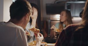 Close-up happy young multiethnic student friends having pizza and talking at relaxed casual house party slow motion. stock video footage