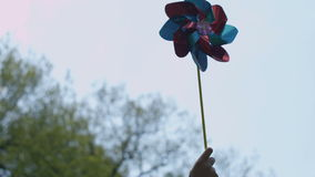 Close up of a happy young woman holding pinwheel in sunny park. stock footage