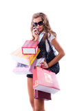 Close-up of happy young woman on a shopping spree. Talking by phone Isolated on white background royalty free stock photo