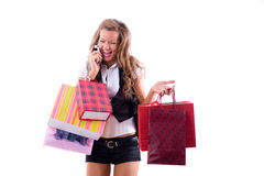 Close-up of happy young woman on a shopping spree. Talking by phone Isolated on white background Stock Image