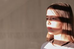 Close up hard light portrait of tween girl with stripe shadows on her face. royalty free stock photo