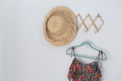 Hat and dress hanging against white wall Royalty Free Stock Image