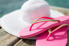 Close up of hat and slippers at seaside Stock Photos