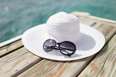 Close up of hat and sunglasses at seaside Royalty Free Stock Photos