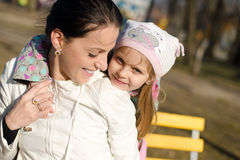 Close up on having fun playing together beautiful little girl with her mother in spring or autumn park outdoors copy space Royalty Free Stock Photos