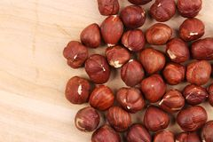 Close up of hazel nuts on a wooden board. Royalty Free Stock Photos