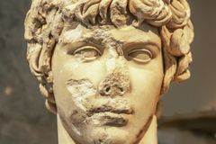 Close-up of head of ancient marble statue of attractive Greek youth with parts of face chipped off and destroyed stock images