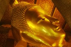 Close up head of golden statue of ancient laying Buddha in the temple of Bangkok, Thailand. stock photo