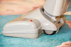 Close up of the head of a modern vacuum cleaner being used while vacuuming a thick pile white carpet Stock Photos