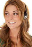 Close up head phones. A woman with a smile on her face listening to her head phones Royalty Free Stock Photography