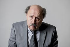 Close up head portrait of bald 60s senior business man sad and depressed looking funny and messy in sadness emotion stock image