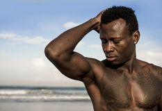 Portrait of young attractive and fit black afro American man with strong muscular body posing cool model attitude on the beach. Close up head and shoulders royalty free stock photo