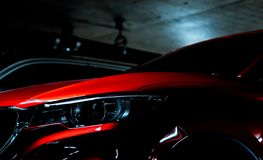 Close up headlight of shiny red luxury SUV compact car parked in shopping mall underground parking lot. Elegant electric car. Technology and business concept Royalty Free Stock Photography