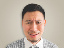 Close up of headshot of crying face man. Close up of straight face of crying Asian man with light beard. isolated on cream colour background Stock Photo