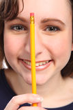 Close up headshot of happy young girl with pencil Stock Photo