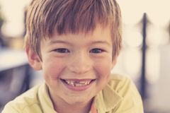 Close up headshot portrait of young little 7 or 8 years old boy with sweet funny teeth smiling happy and cheerful in joy face expr Royalty Free Stock Image