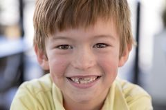Close up headshot portrait of young little 7 or 8 years old boy with sweet funny teeth smiling happy and cheerful in joy face expr stock images
