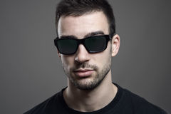 Close up headshot of serious young handsome man wearing sunglasses Royalty Free Stock Image