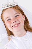 Young girl's First Communion. A close-up/headshot, shot straight on, of a young girl smiling in her First Communion Dress and Veil Stock Image