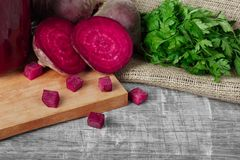 Whole and sliced beetroots, parsley and beverage on a cutting board and on a wooden background. Vegetables from a garden stock image