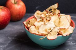 Close-up healthy  apple chips in turquoise ceramic bowl and two whole apples on dark grey background. stock photo