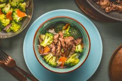 Close up of healthy balanced nutrition meal in bowl with beef meat, rice , steamed vegetables: broccoli and carrots served with pl. Ate and cutlery, top view royalty free stock photos