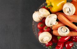 Fresh raw vegetables. Close up healthy fresh salad ingredients with carrot, mushroom, tomato and bell pepper on glass  bowl, placed on dark stone kitchen table Stock Photos