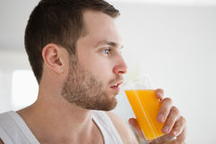 Close up of a healthy man drinking orange juice. In his kitchen Royalty Free Stock Photo