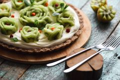 Close up of healthy raw vegetarian dessert. Homemade pie with kiwi roses, berries and cream filling on nutty crust served with. Forks and carved kiwis on blue royalty free stock photos