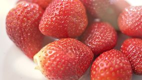 Close-up heap of fresh fragrant red strawberry surrounded by summer light sunbeams panning shot