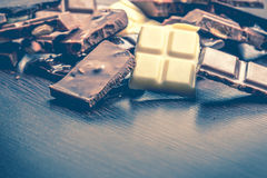 Close up of a heap of various chocolate pieces over dark wood background. Dark, milk, white and nuts chocolate bars. Copy space. V Royalty Free Stock Images