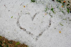 CLOSE UP HEART DRAWING ON LARG FRESHLY HAIL STONES IN GRASS. CLOSE UP TEXTURE HEART DRAWING ON LARG FRESHLY HAIL STONES IN GRASS royalty free stock photography