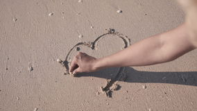 Close-up heart in the sand. Woman`s hand draws a heart stock video footage