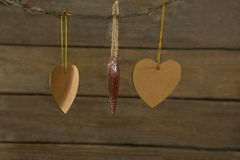 Close up of heart shape decoration hanging on rope. Against wooden wall Stock Photos