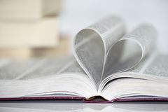 Close-up of heart shape from paper book against white background. Love for the books stock photography
