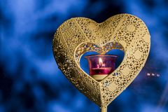 Close up of heart shaped candle holder with pink glass light burning in the core with blue winter background with strong bokeh. royalty free stock images